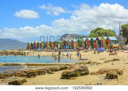 Cape Town, South Africa - January 10, 2014: the popular retro Muizenberg Beach in Cape Town located in the Indian Ocean, crowded on weekends, with its famous colorful Victorian bathing boxes.
