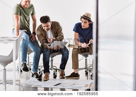 What is it. Puzzled young man is pointing finger at laptop while his colleague are looking at screen with misunderstanding. Various graphics are on floor