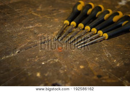 Set of torx screwdrivers with rubber handles on top of an old wooden workbench.