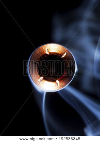 Copper jacketed hollow point and smoke on a black background