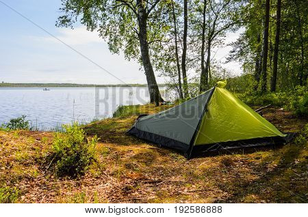 Overnight in a green tent near lake in forest.