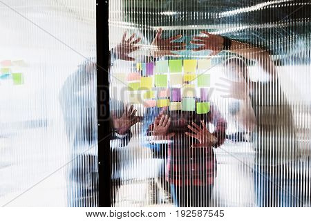 Joyful young colleagues are reading ideas on stickers while leaning hands on glass wall. Focus on their palms