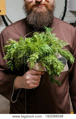Chef with bouquet of dill and parsley, man with beard, cooking, green salad concept