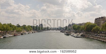 ParisFrance- April 29 2017: Bridge Leopold Sedar Senghor. Tourists stroll across the bridge and at the bridge. On the river ships sail and are much at the piers
