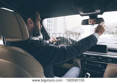 Young business person test drive new vehicle straighten mirror