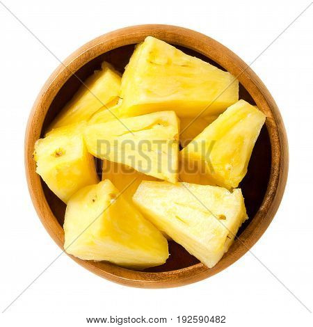 Pineapple pieces in wooden bowl. Ananas comosus, the edible multiple fruit of a tropical plant, consisting of coalesced berries. Yellow flesh. Macro food photo close up from above on white background.