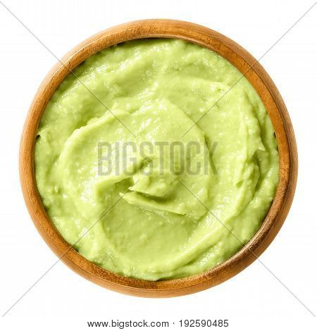 Avocado cream in wooden bowl. Alligator pear, the fruit of the Persea americana tree. Light green paste of mashed avocados and lemon juice. Macro food photo close up from above on white background.