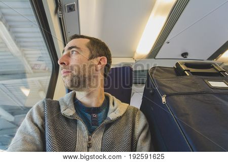 Young Man Traveling On A Train And Looks Out The Window