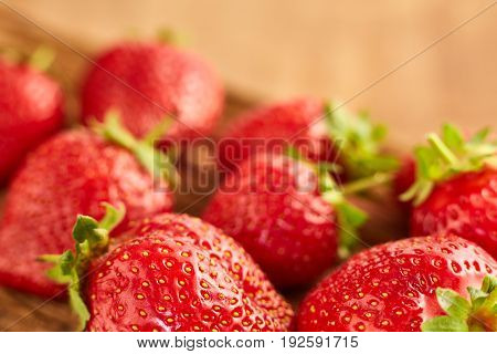 Close-up of the fresh red strawberries on the brown wooden table. Big appetite strawberries. Horizontal photo. Food backgrounds and still-life. Tasty, useful and natural product. Concept of the vitamin food.