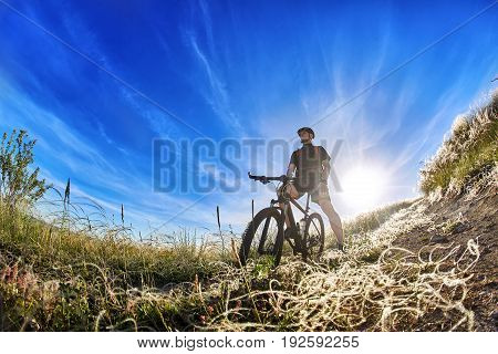 Low angle view of cyclist standing with mountain bike on trail at sunrise. Attractive sportsman in the sportwear and with helmet. Horizontal photo and fisheye. Travel in the countryside. Concept of the healthy lifestyle.