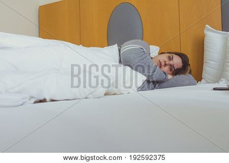 Young Woman Daydreaming While Lying On Bed Under The Blanket