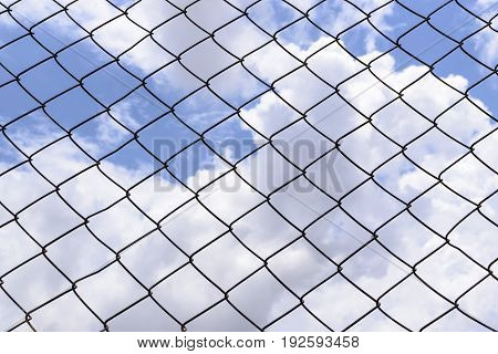 Metallic fence against the blue sky with clouds.Net metallic pattern barrier against blue sky. Chain Link Fence against  Cloudy Blue Sky.