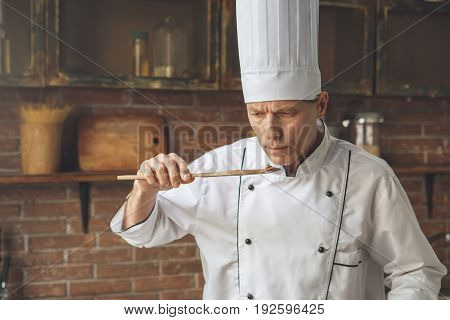 Mature male professional chef cooking meal indoors taste food