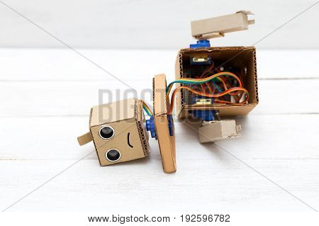 sad broken robot on white wooden background