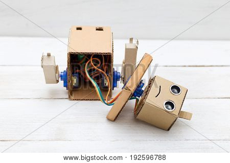 broken robot with hands on the white wooden background