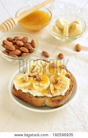 Toast with cream cheese topped with banana almonds and honey, vertical