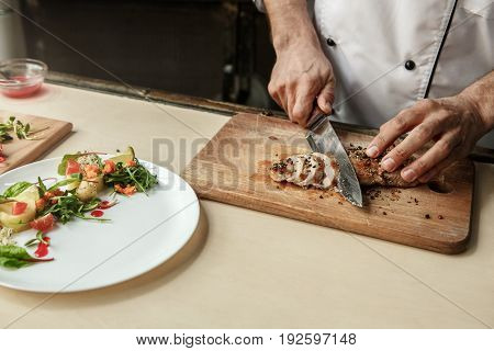 Mature male professional chef cooking meal indoors cutting meat