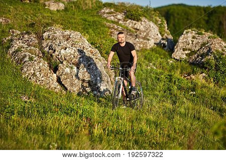 Attractive cyclist riding the bike on summer trail near beautiful big rocks. Young sportsman in the balck sportwear and with sportive shoes. Beautiful summer landscape. Concept of the healthy and active lifestyle.