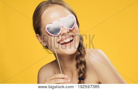 Smile, laugh, young woman on a yellow background, accessories for parties and holidays.