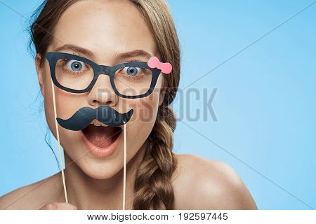Girl on a blue background holds paper accessories for parties, holiday, emotion, surprise, joy.