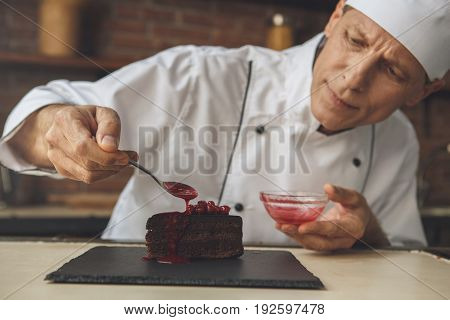 Mature male professional chef cooking meal indoors dessert