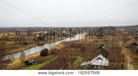 Beautiful autumn landscape with a Russian village Selco-Karelian Msta on the shore of the river. Russia, Tver Region, Udomlya district.