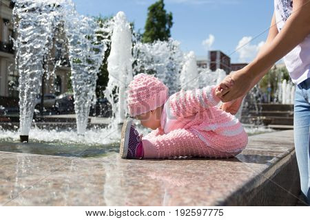 The baby is playing at the fountain