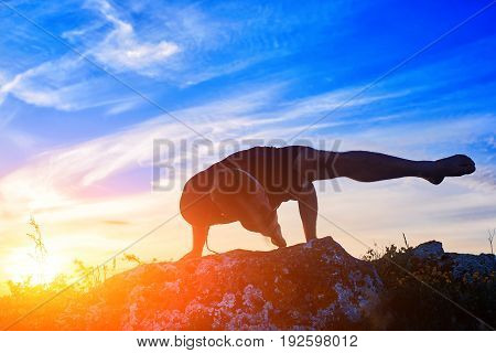 Attractive man doing yoga on the rock in the morning against sunrise. Young sportsman in the black sportwear and barefoot. Beautiful blue sky with clouds. Practicing yoga on the nature. Concept of the healthy lifestyle.