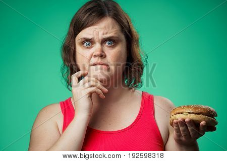 Fat, woman on a green background holds a hamburger, fast food, diet, health, beauty.