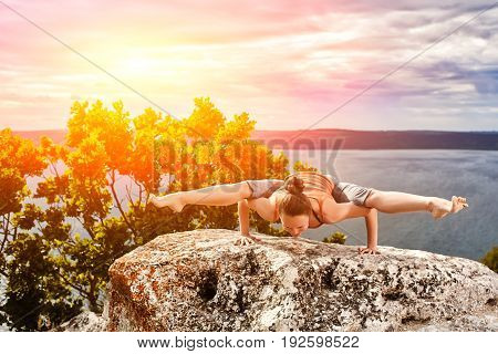 Young woman doing yoga fitness exercises outdoor in river landscape. Sportive woman in the t-shirt, leggings and barefoot. Beautiful sky with clouds, big river and rocks. Concept of the healthy lifestyle.