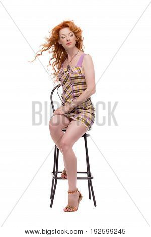 Fulllength shot of redhead sitting with eyes closed.