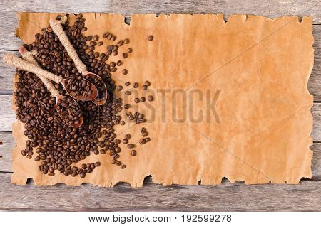 Coffee beans and wooden spoons on an old sheet of paper close-up