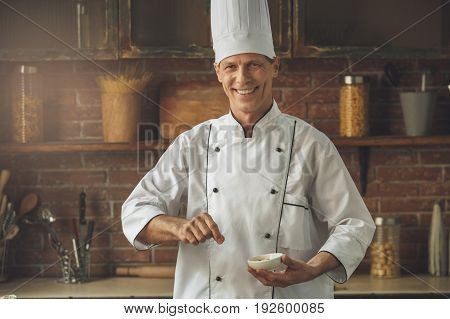 Mature male professional chef cooking meal indoors salt