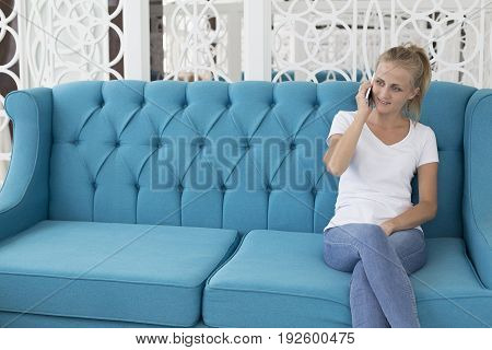 Young caucasian woman talking on mobile phone and sitting on blue sofa