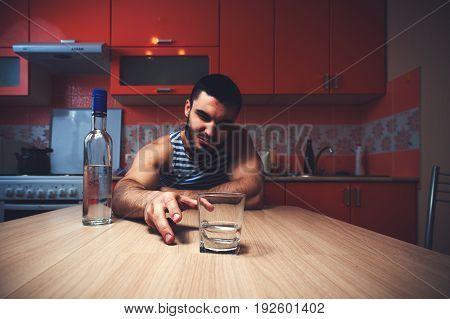 Young caucasian man drinking alcohol at home. Drunken male adult sitting at the table with glass and bottle. Alcohol abuse.