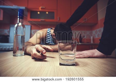 Sad depressed alcoholic man sitting at the table. Unrecognizable person staying next to. Alcohol addiction.