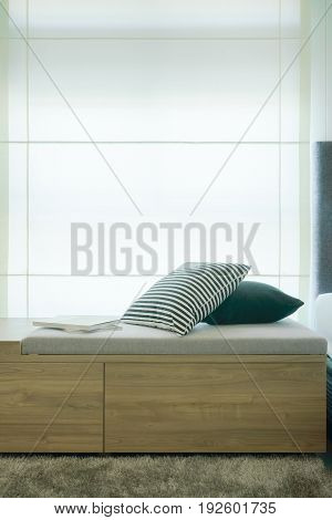Pillows And Books On Cushion Next To Window In Modern Style Interior Bedroom