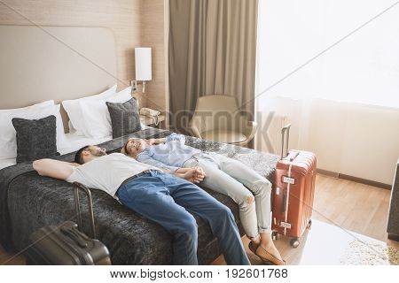 Young man and woman together tourism hotel lying on bed