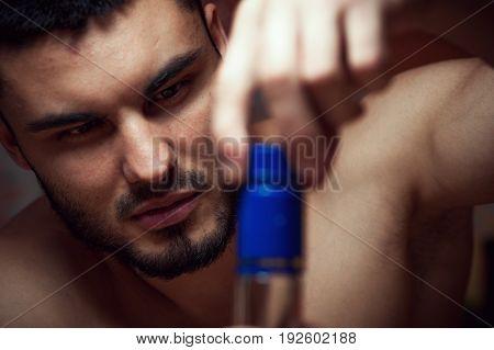 Closeup of young drunken man opening alcohol bottle. Alcoholic addiction