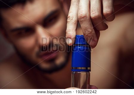 Young caucasian man drinking alcohol at home. Drunken male adult opening bottle. Alcohol abuse.