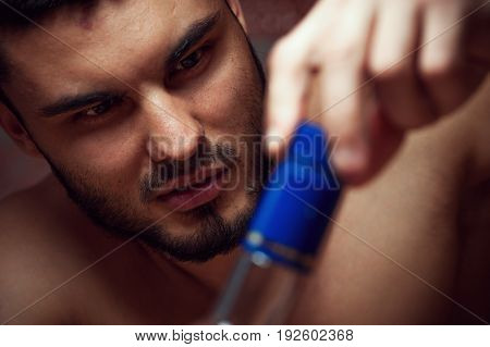 Closeup of male adult opening alcohol bottle. Alcohol abuse.