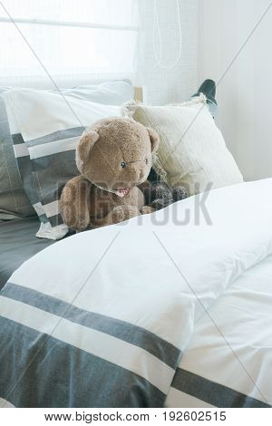 Brown Bear And Pillows On Bed In Child's Bedroom