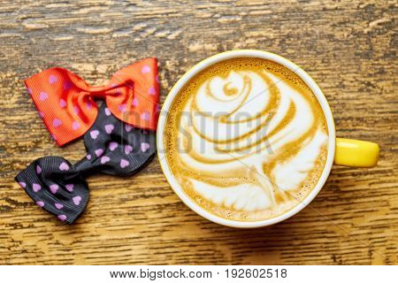 Coffee and two bow ties. Rose latte art.