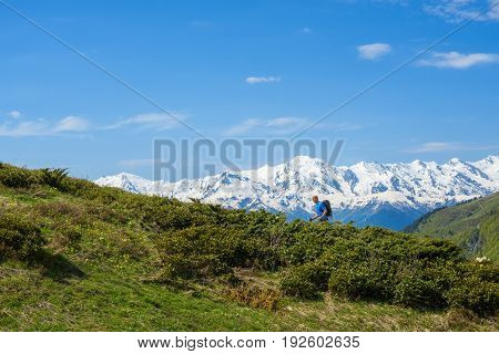 Traveler Ascends The Green Slope Against The Background Of Snow-capped Mountain Peaks