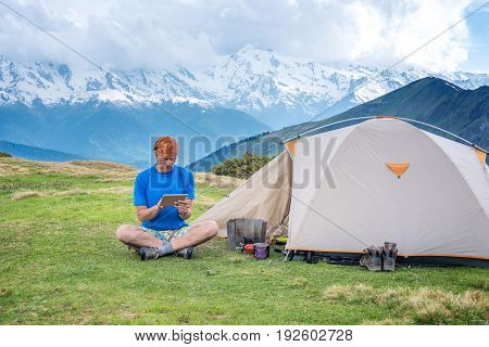 Traveler Sits Next To The Tent, In The Mountains Using A Tablet