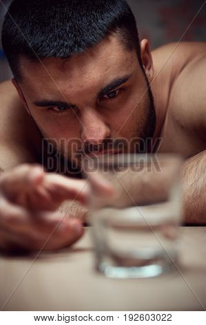 Depressed alcoholic man lying on the table with glass of vodka. Alcohol addiction.