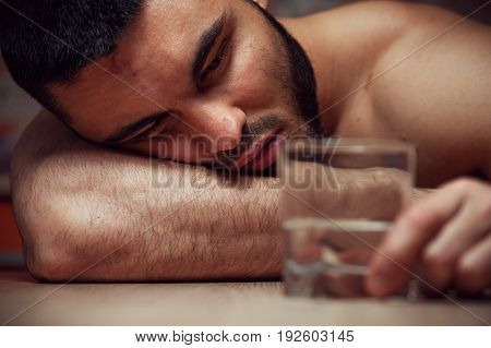Drunken young man sleeping at the table with glass. Alcohol addiction. Shallow depth of field.