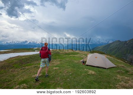 Man Hurries To The Tent Before The Thunderstorm Begins In The Mountains