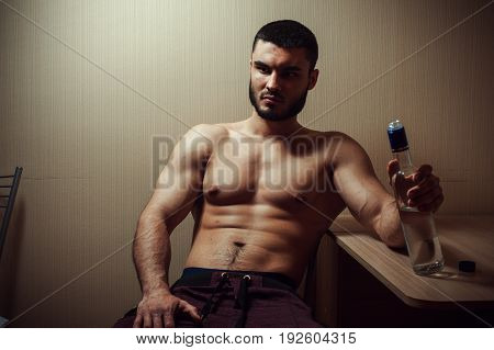 Depressed alcoholic man sitting at the table with glass of vodka. Alcohol addiction.