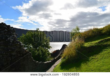 Crumbling stone wall encompassing the grounds of Urquhart Castle in Scotland.
